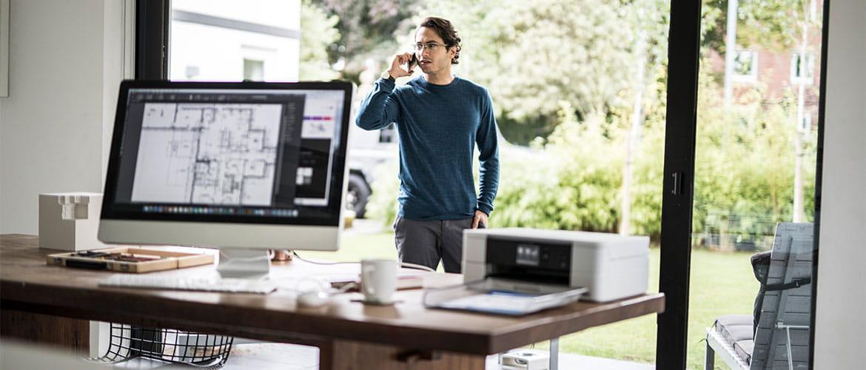 Mann telefoniert im Home Office, Bildschirm und Drucker im Vordergrund