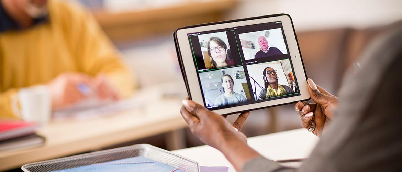 Frau hält Tablet mit Videokonferenz