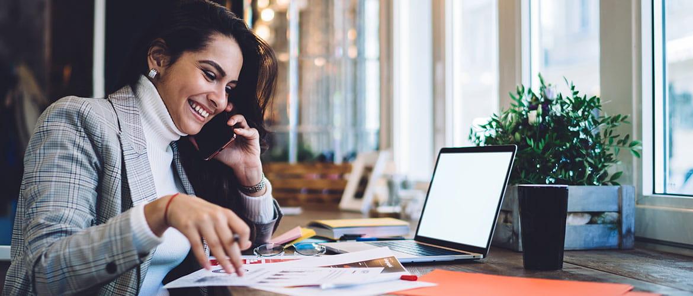 Frau telefoniert in einem Cafe. Auf dem Tisch steht ein Laptop und Dokumente.