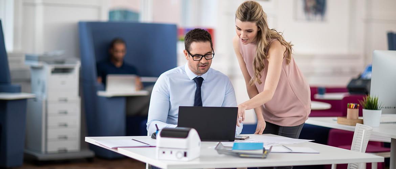 Frau erklärt Mann etwas an Laptop Bildschirm im Büro.