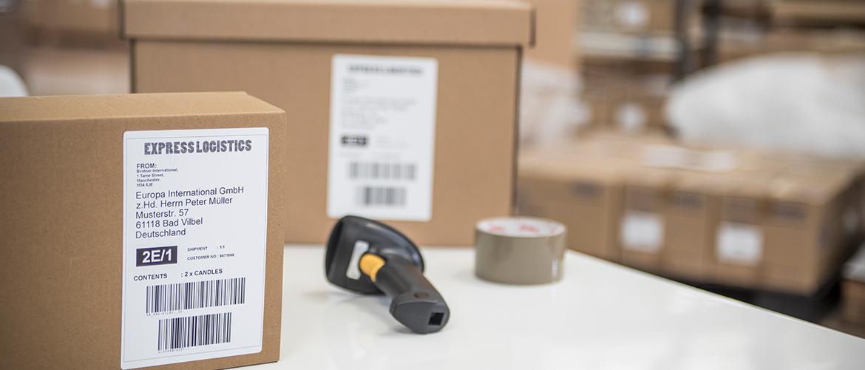 Versandkartons im Lager mit Versandetiketten und Barcode-Scanner