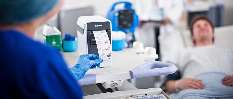 Krankenpflegerin entnimmt Barcode-Etikett aus Drucker mit Patient im Hintergrund.