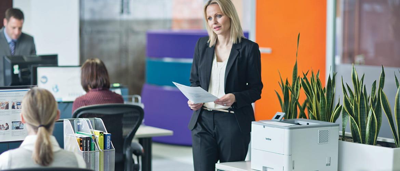 Frau in Büro holt Ausdruck aus Abteilungsdrucker ab.
