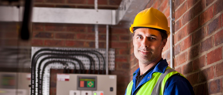 Elektrofacharbeiter in Warnweste und gelbem Helm , lächelt in Kamera, Schaltkasten im Hintergrund