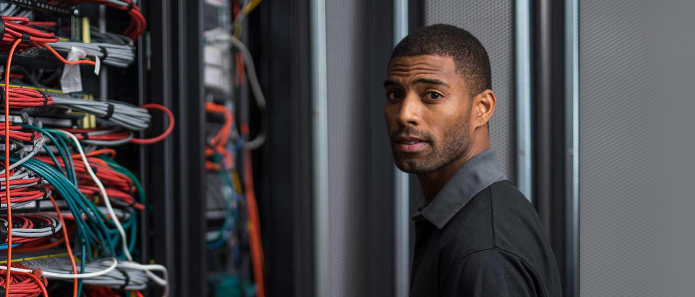 Netzwerkspezialist vor Kabelschrank stehend