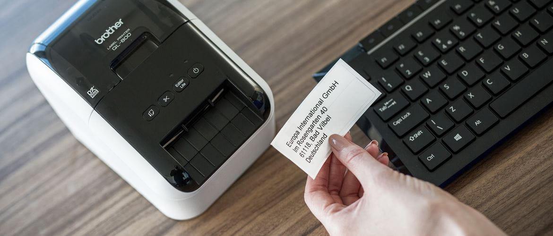 Brother QL-Etikettendrucker auf dunkelbraunem Schreibtisch neben schwarzer Tastatur stehend, Hand hält gedrucktes Etikett