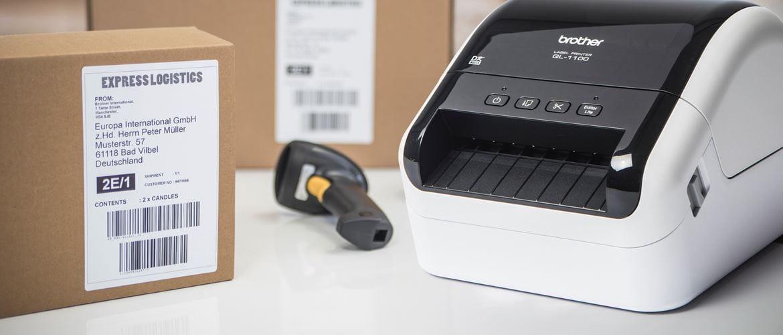 Brother Etikettendrucker auf Tisch stehend neben Paket mit gedrucktem Versandetikett, weitere Pakete und Klebebandrolle im Hintergrund