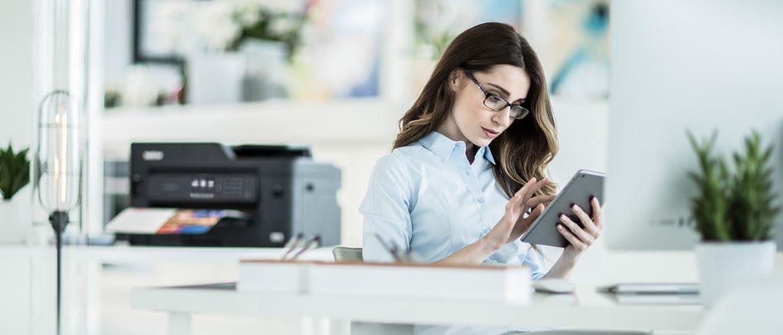 Büromitarbeiterin sitzt an Schreibtisch und druckt mit iPad auf Brother Drucker im Hintergrund