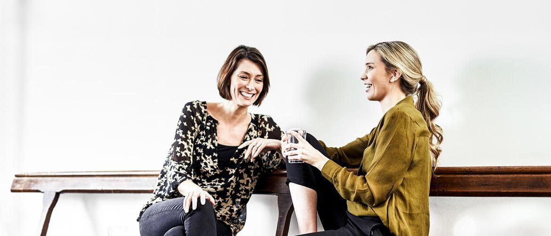 Zwei Frauen, im entspannten Gespräch, auf Bank sitzend und lächelnd