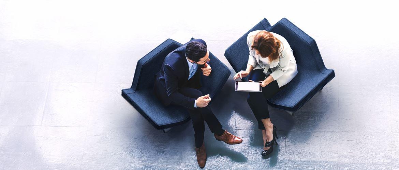 Mann und Frau im Gespräch aus Vogelperspektive, Tablet haltend, in zwei Sesseln sitzend