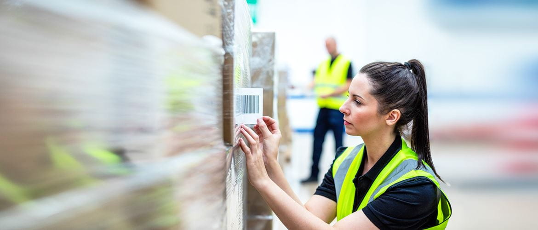 Frau in Warnweste klebt Barcode-Label auf verpackte Pakete