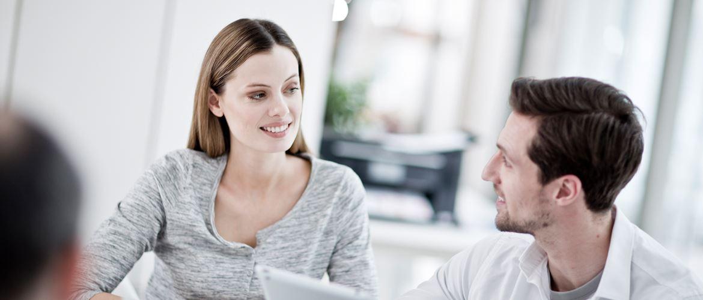 Mann und Frau vor Laptop lächeln sich an, Drucker im Hintergrund