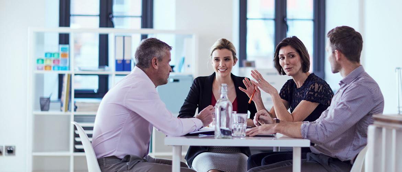 Zwei Geschäftsfrauen und zwei Geschäftsmänner saßen an einem Tisch und diskutierten eine Frage.