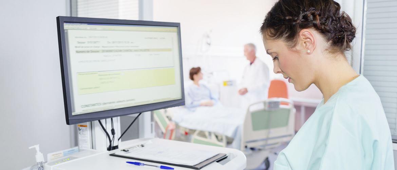 Krankenschwester an Bildschirmarbeitzplatz, Patient und Arzt im Hintergrund