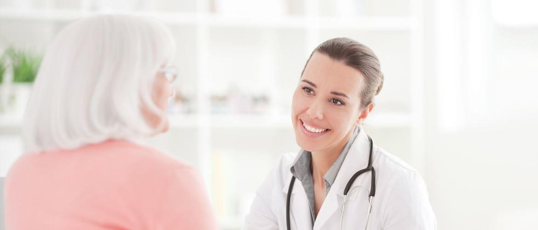Ärztin im Gespräch mit Patientin, lächelnd