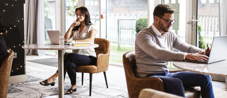 Personen am Tisch in einem Bistro am Tisch mit Computer