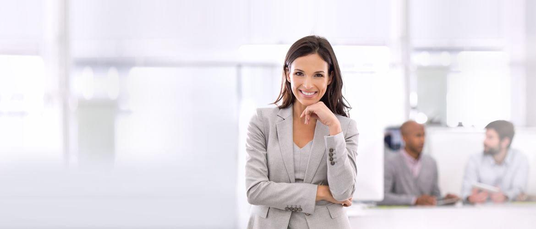 Frau in Büro-Umgebung, lächelnd in Kamera blickend, Kollegen im Hintergrund im Gespräch