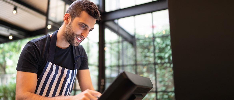Restaurantmitarbeiter gibt Daten in Kasse ein, lächelnd