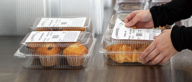Hände kleben Brother Etikett auf Lebensmittelverpackung, Muffins und Croissants