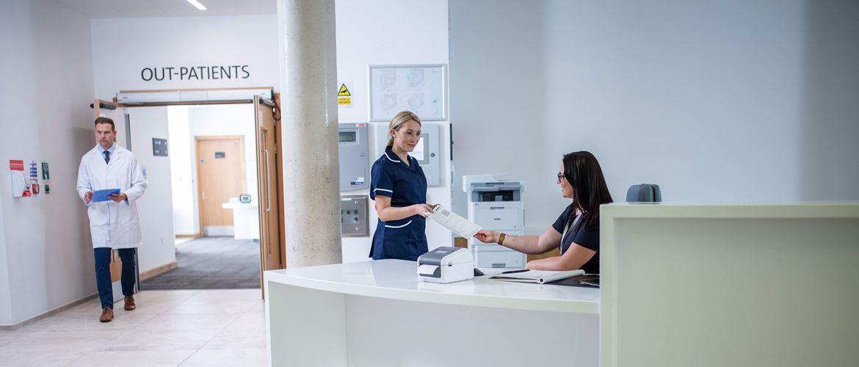 Artzhelferin am Schreibtisch, während eine Krankenschwester und der Arzt im Hintergrund arbeiten.