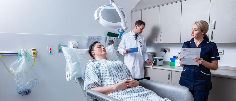 Patientin liegt im Behandlungszimmer und unterhält sich mit einer Krankenschwester, der Arzt im weißen Kittel druckt ein Etikett aus.