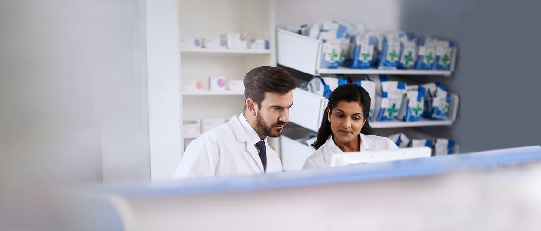 Zwei Krankenhausmitarbeiter vor Regal mit Medikamenten.