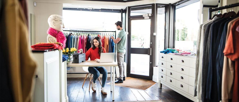 Mann kauft Kleidung ein und Frau sitzt am Schreibtisch und druckt Dokument in einem Kleidungsgeschäft