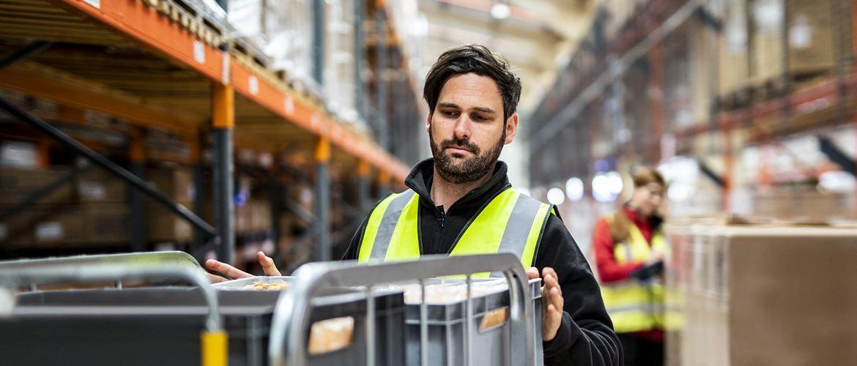 Mann in schwarzem Pullover und Warnweste stapelt Kisten auf Transportwagen, Frau an Lagerregal im Hintergrund