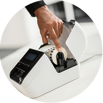 Etikettenrolle wird in Brother QL-Desktopdrucker eingesetzt.