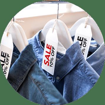 Rote und schwarze Verkaufsetiketten auf Kleiderbügeln für Jeanshemden.