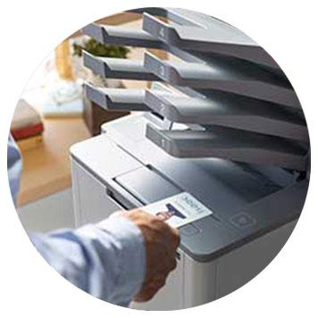 Hand hält Chipkarte an Brother Multifunktionsgerät mit mehreren Ausgabefächern
