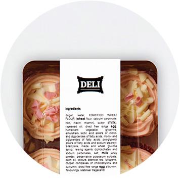 Rosa und weiße Cupcakes in einer weißen und durchsichtigen Plastikbox mit einem Zutatenetikett
