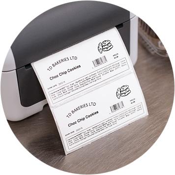 Grau, weißer Brother-Etikettendrucker auf Edelstahlbank mit bedrucktem Etikett