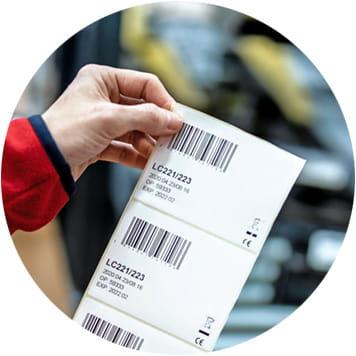 Logistikmitarbeiterin in rotem Pullover hält mehrere Barcode-Etiketten, Transportband mit etikettierten Päckchen im Hintergrund