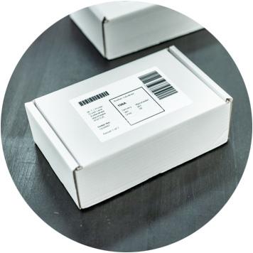 Weiße Kartons mit Brother Versandetiketten auf dunkelgrauem Transportband