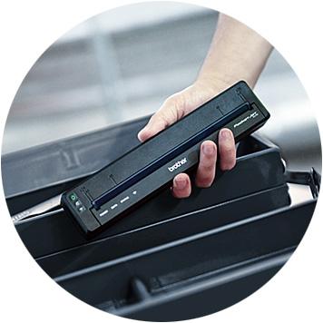 Hand, die den mobilen Brother PJ-7 über einen roten Werkzeugkoffer hält