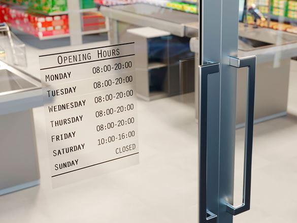 Strapazierfähige Brother P-Touch-Etiketten auf gläserner Ladentür zur Anzeige der Öffnungszeiten