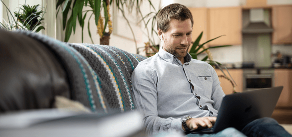 Mann, der von zu Hause aus arbeitet, auf Sofa sitzend mit Laptop