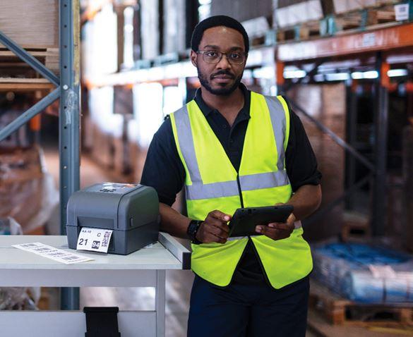 Logistik-Mitarbeiter in Lagerhalle an Tisch stehend, freundlich lächelnd mit Tablet und TD-4T Etikettendrucker