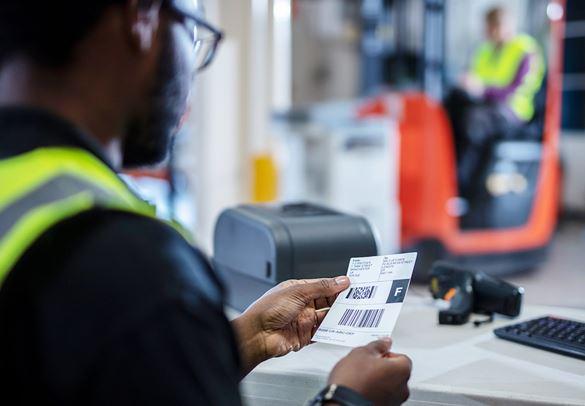 Logistikmitarbeiter an Arbeitsplatz sitzend, hält gedrucktes Brother-Versandetikett in der Hand, Gapelstapler im Hintergrund