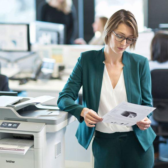 Frau in Businesskleidung, an Brother Multifunktionsgerät stehend, betrachtet Ausdruck