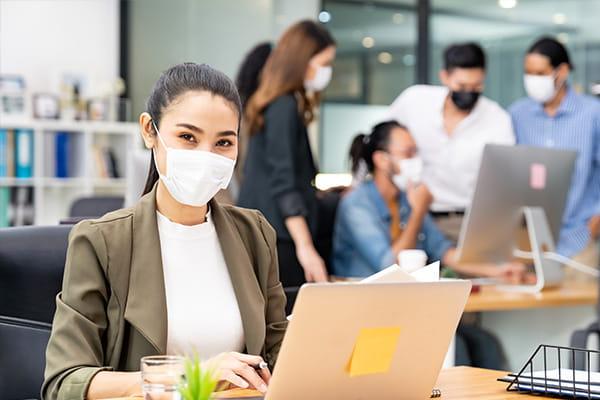 Frau am Computer mit Maske im Büro