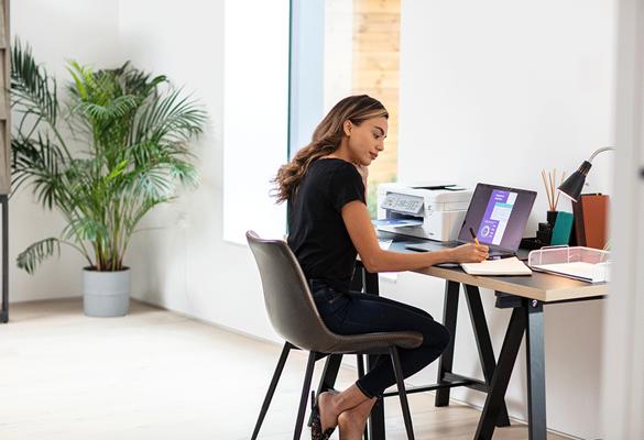 Frau, die zu Hause mit MFC-J4340DW am Schreibtisch mit Laptop arbeitet