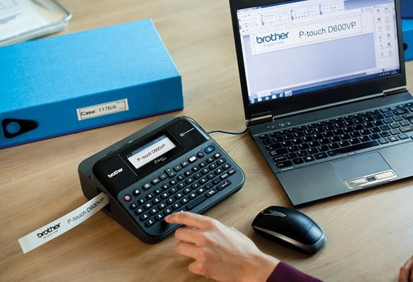 P-touch label printer on an office desk, connected to a laptop, with a label printing