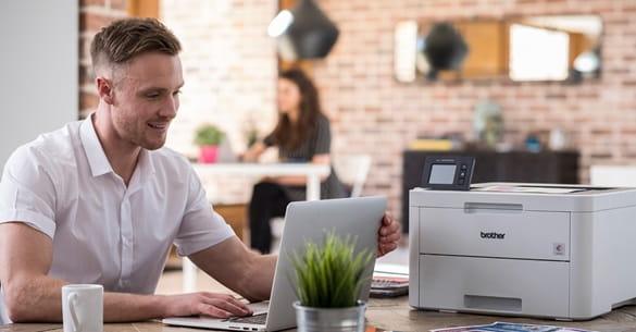 Mann sitzt neben einem Drucker an einem Laptop.