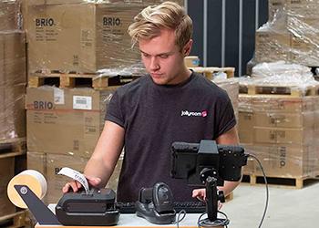 Lagerfachkraft druckt ein Versandetikett an einem mobilen Drucker aus.