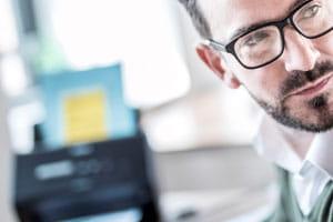 Mann im Büro mit Scanner im Hintergrund