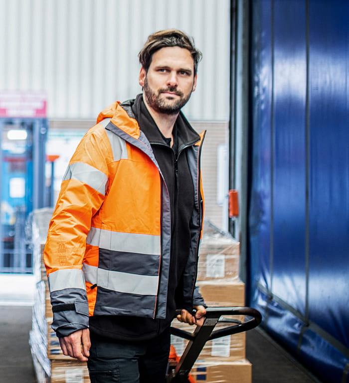 Mann mit orangefarbener Warnschutzjacke zieht Hubwagen mit Palette und Kisten im LKW mit blauen Seiten