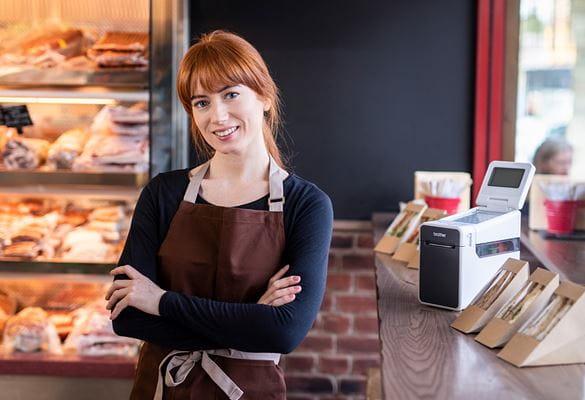 Restaurantmitarbeiterin im Restaurant im Portrait, freundlich lächelnd, TD-Etikettendrucker mit Sandwiches daneben