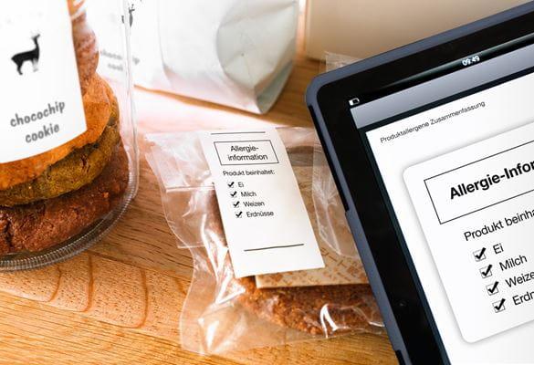Tablet mit Menüverwaltungssoftware und Cookies mit Lebensmitteletiketten im Hintergrund
